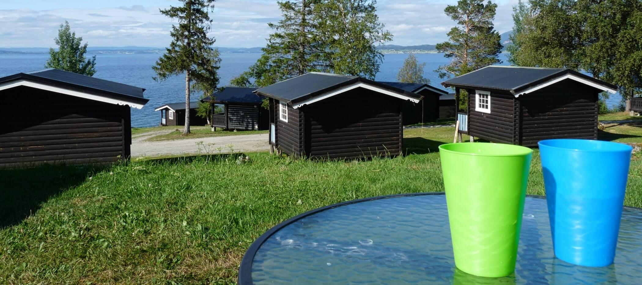 Campingplatz in Norwegen mit Hütten und Plastikbecher im Vordergrund