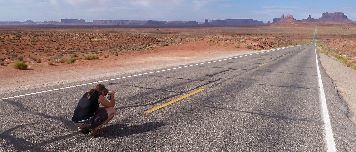 Sabine sitzt auf Straße zum Fotografieren