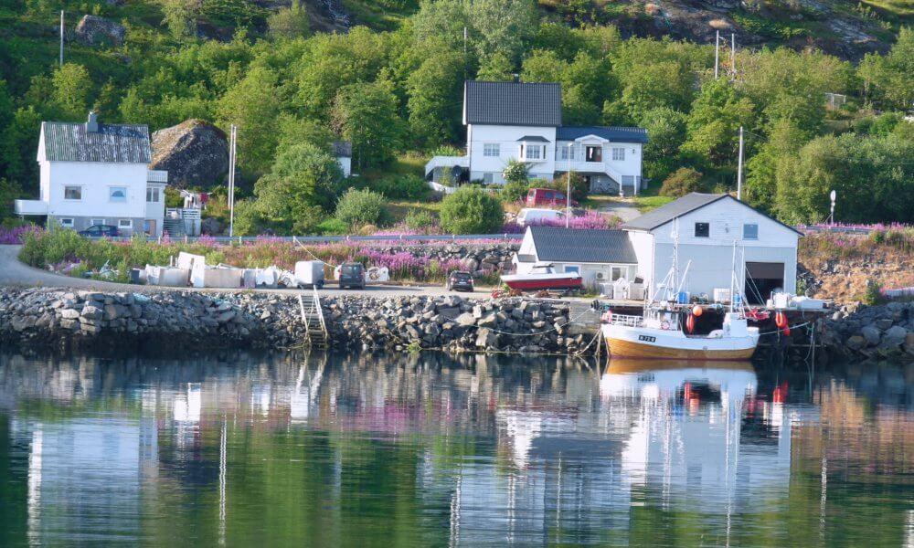 Segelboot vor weißen Holzhäusern