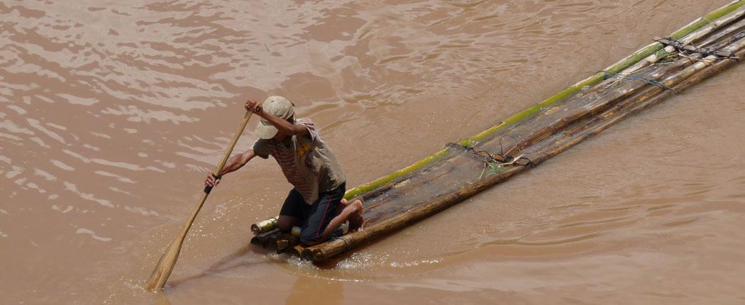 Mann auf dem Floß in Laos