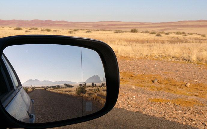 Spiegel eines Mietwagens mi Bergen im Hintergrund