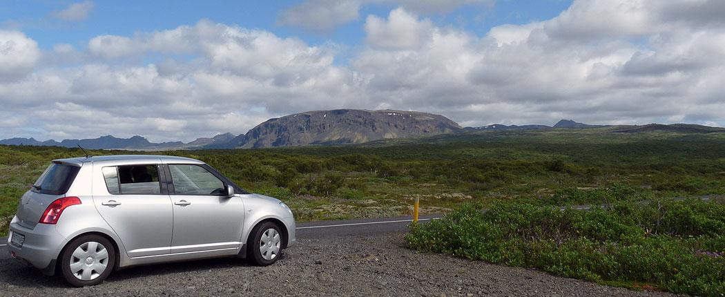 Mietwagen vor Bergkulisse in Island