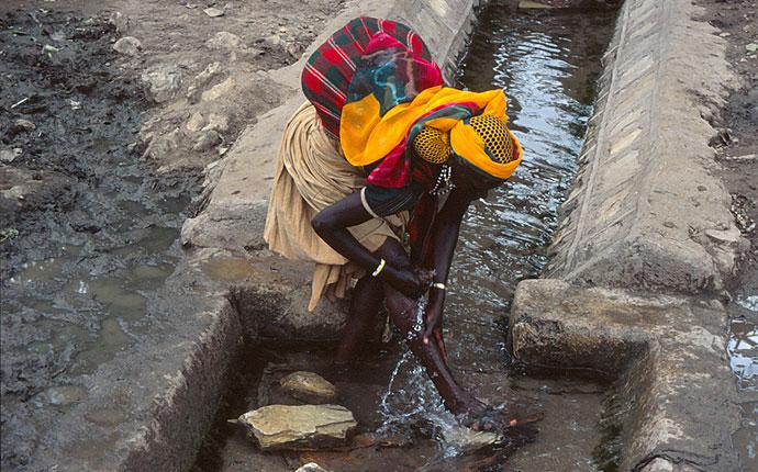 Eine Frau in Äthiopien mit buntem Kopftuch am Wasserloch