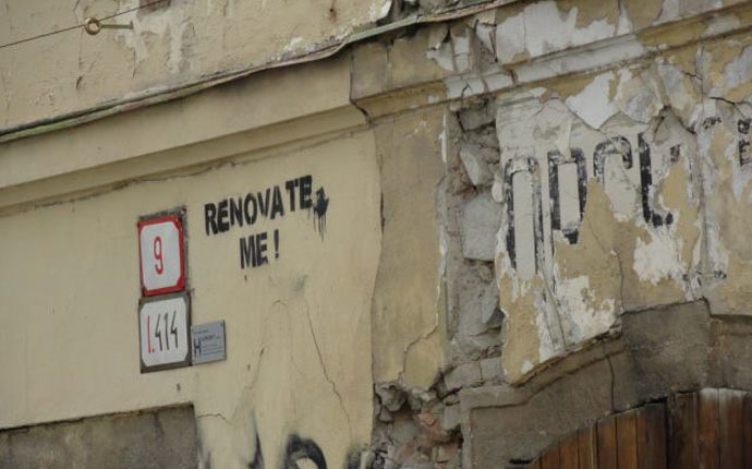 """""""Renovate me""""-Spruch an altem Haus"""