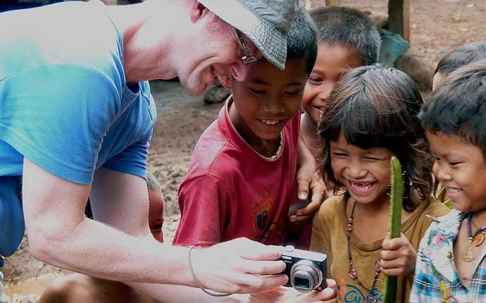 Mann zeigt laotischen Kindern Bilder auf der Kamera