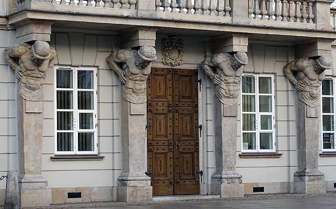 Warschau: Fassade mit vier Säulen mit Männertorso