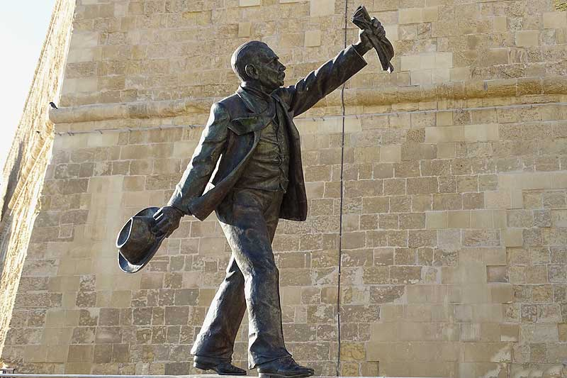 Statue von Mann mit Hut und Zeitung