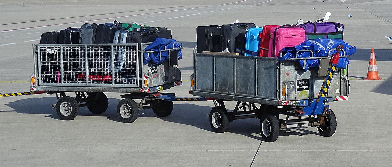Gepäckwagen mit Koffern am Flughafen