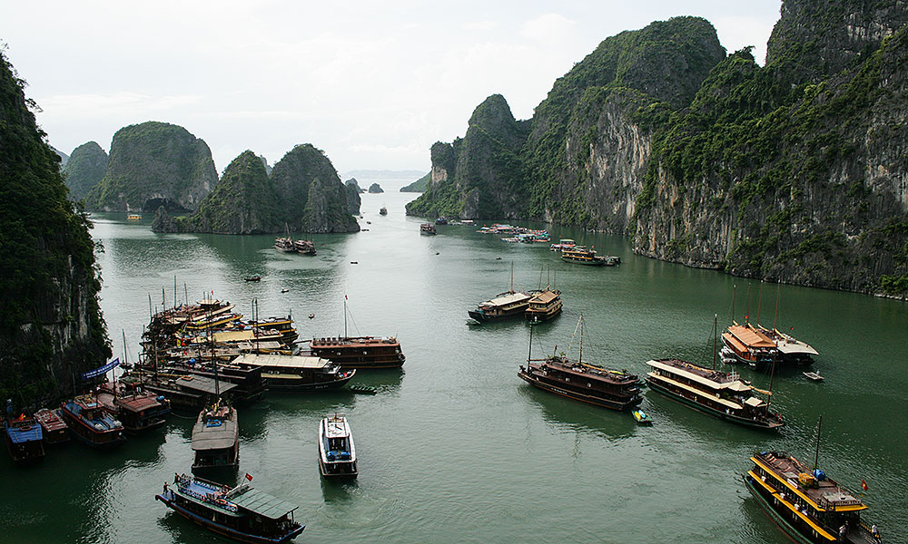 Viele Schiffe vor Felsen in der Halong-Bucht