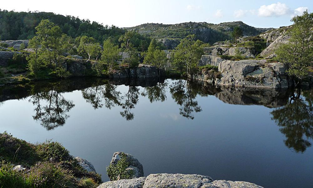 Bergsee mit Felsen am Ufer auf dem Weg zum Preikestolen
