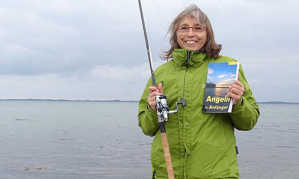 """Sabine mit Angel und Buch """"Angeln für Anfänger"""""""
