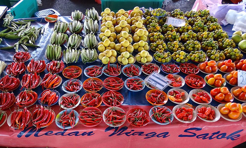 Viele Gemüsesorten auf Tellen auf Markt in Kuching