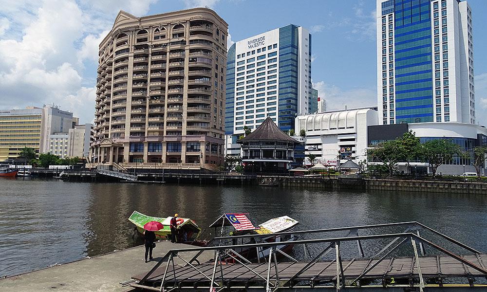 Hochhäuser und alte Boote in Kuching