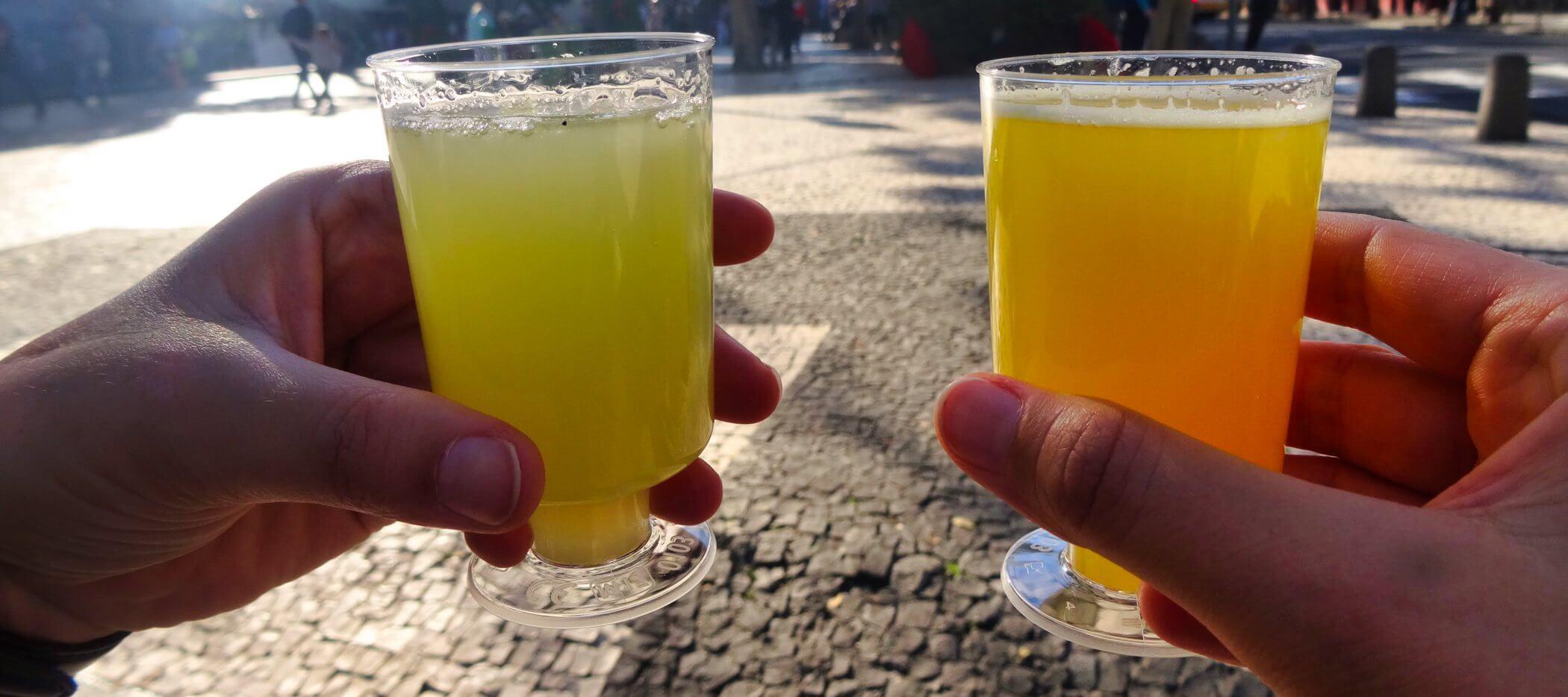 Hände halten Becher mit farbigen Getränken