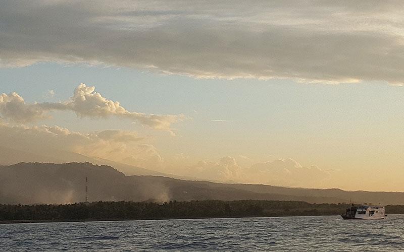 Schiff im Abendlicht fährt an Insel vorbei