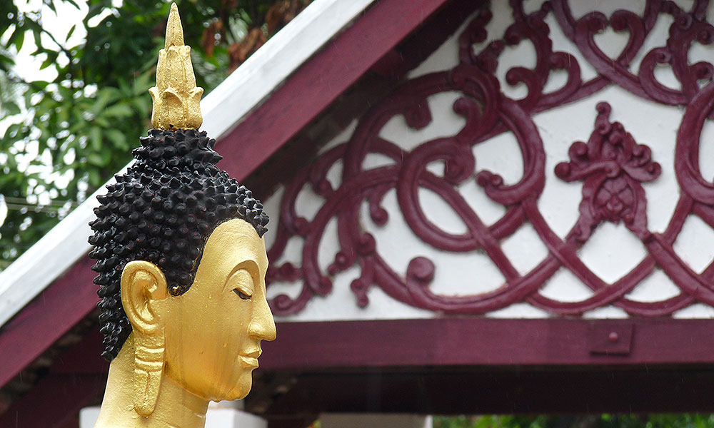 Buddhastatue vor einem Tempel