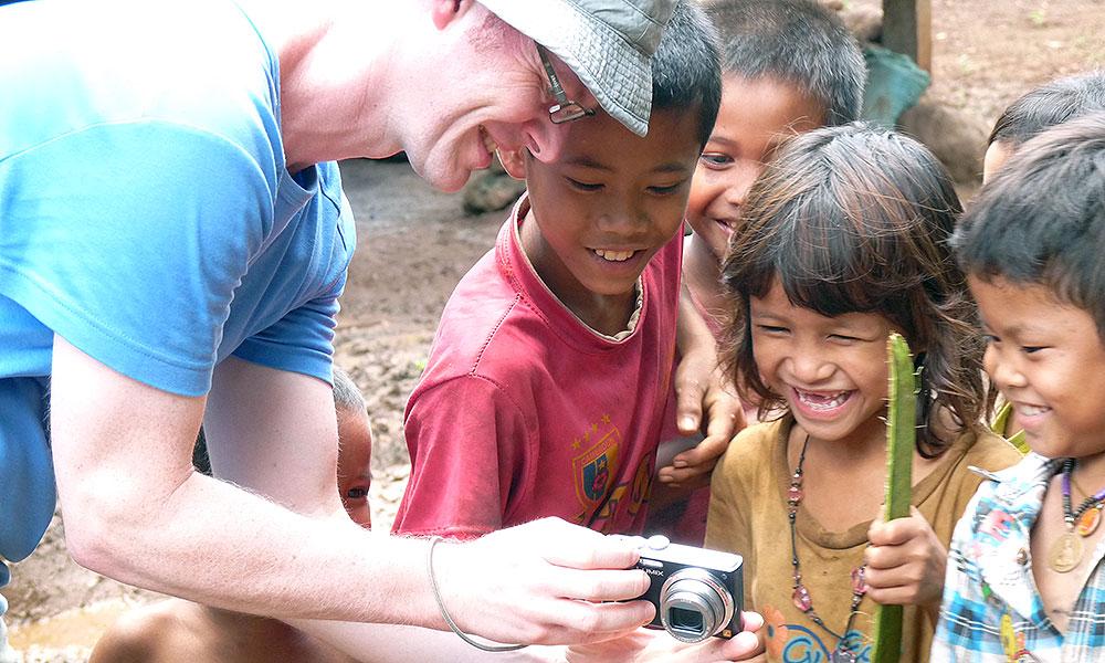 Kinder lachen beim Anschauen des Kameradisplays