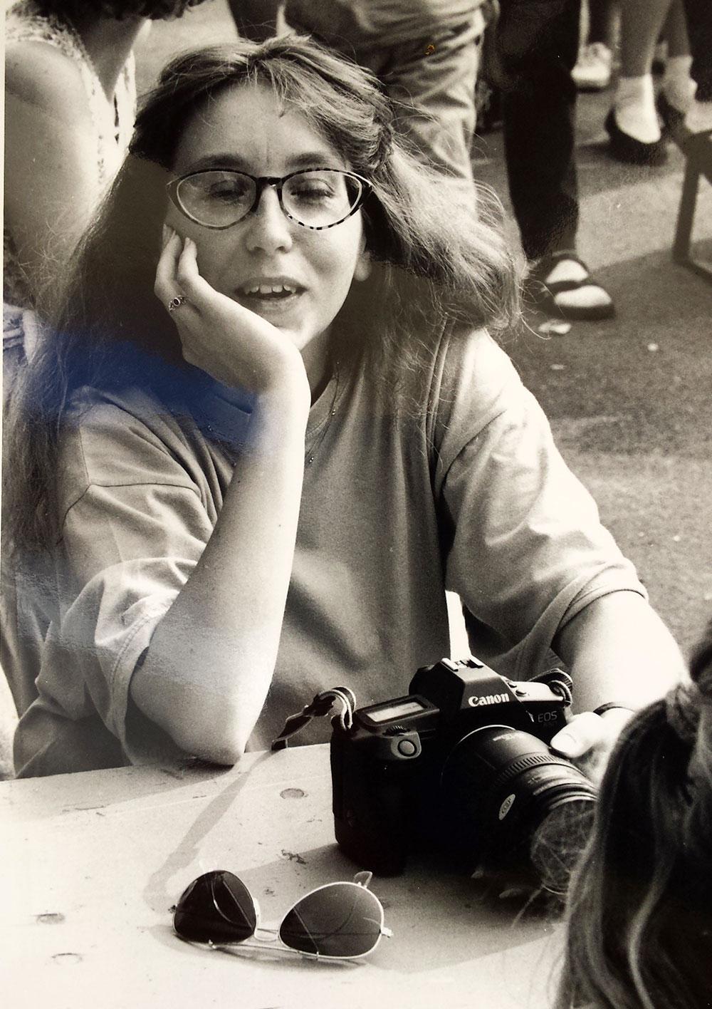 Sabine am Tisch mit einer Kamera vor sich