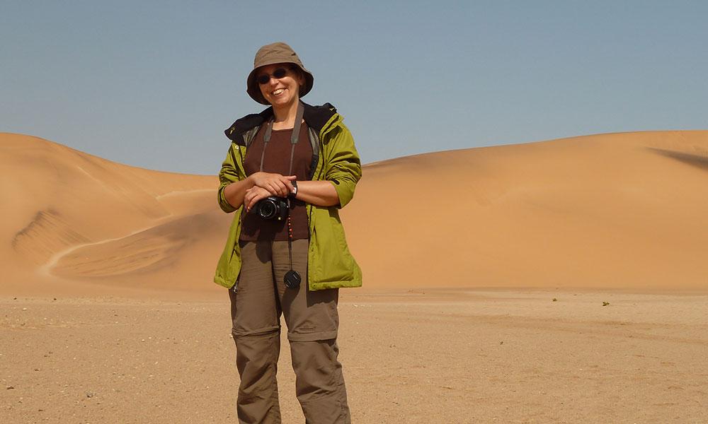 Sabine mit Kamera vor einer Düne