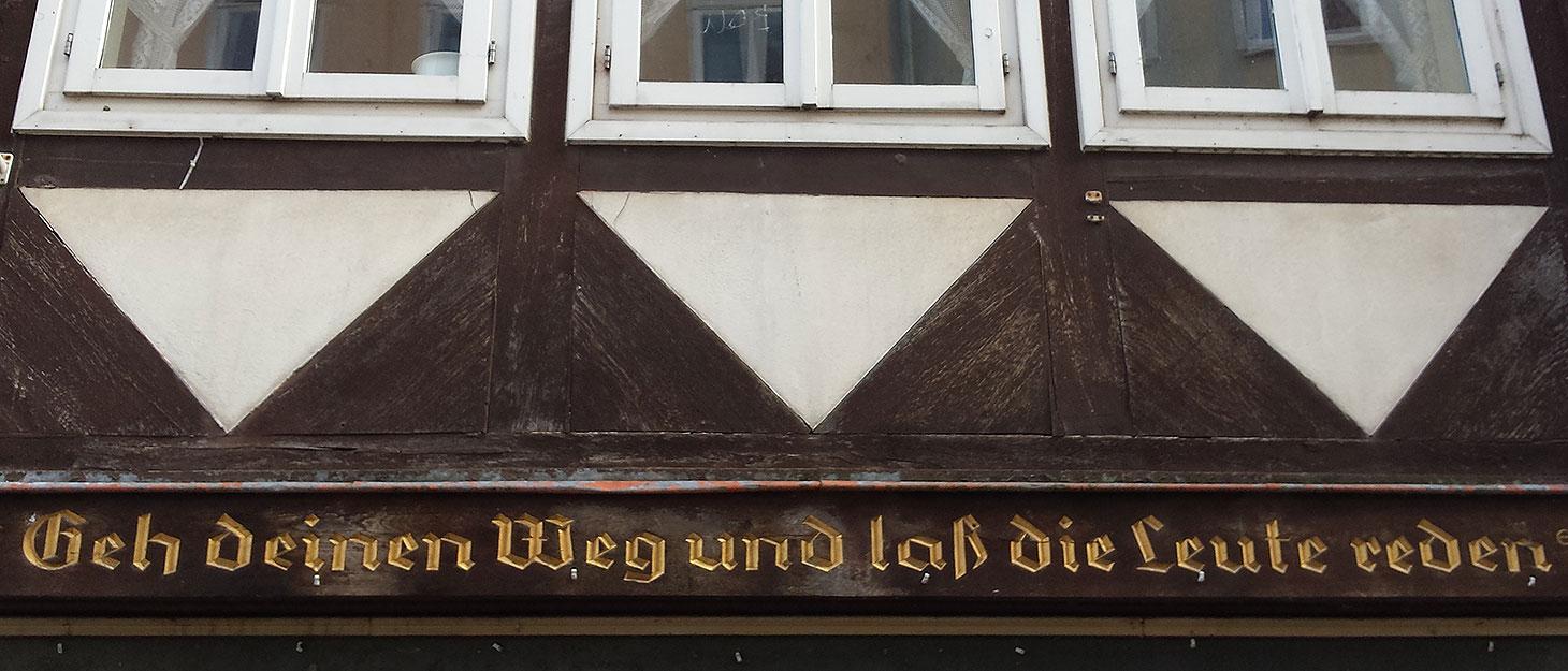 """Spruch am Fachwerkhaus: """"Geh deinen Weg und lass die Leute reden"""""""
