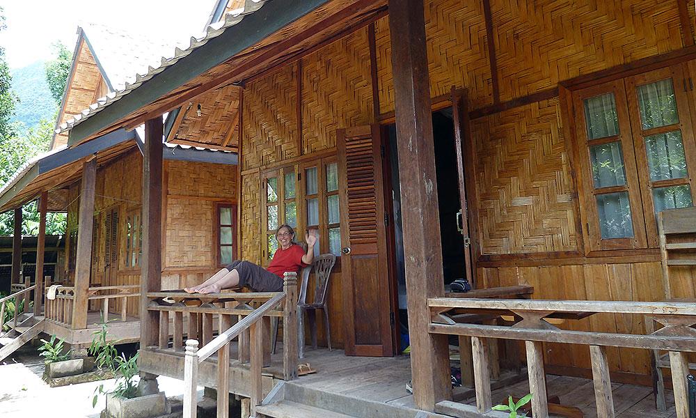 Sabine sitzt vor einer Holzhütte
