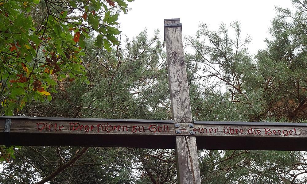 """Kreuz mit Inschrift """"Viele Wege führen zu Gott - einer über die Berge"""""""