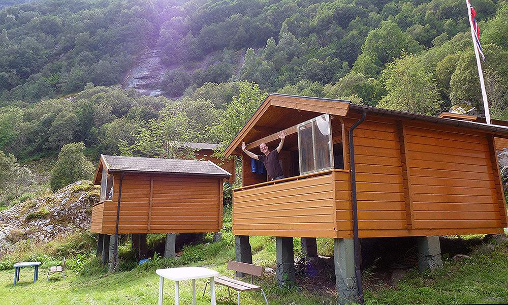 Zwei Holzhütten, Mann auf dem Balkon