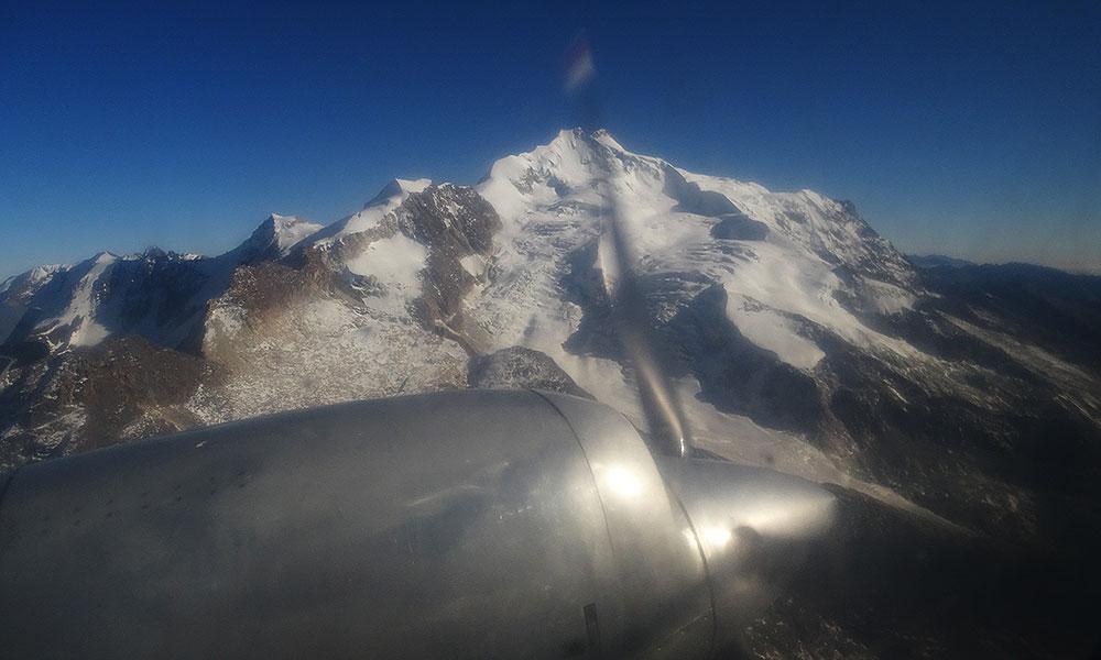 Propellerflugzeug fliegt am Berg entlang