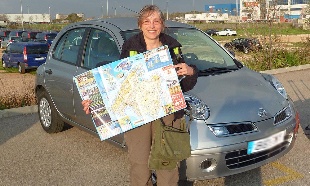 Frau vor Mietwagen mit Mallorca-Karte