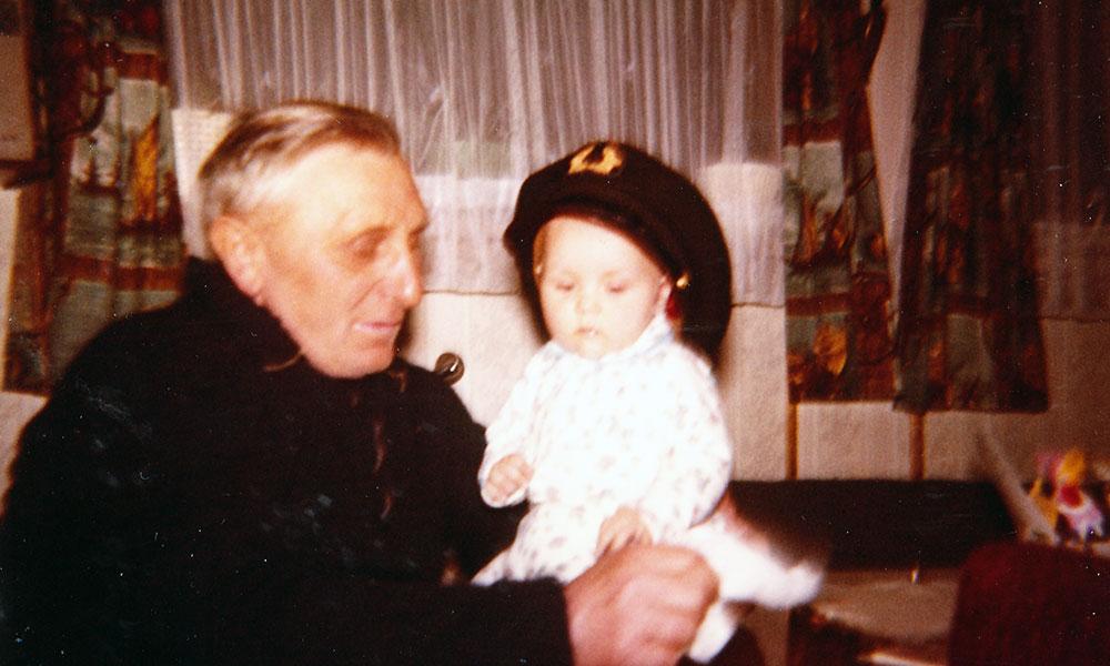 Alter Mann mit Baby, das Schiffermütze aufhat