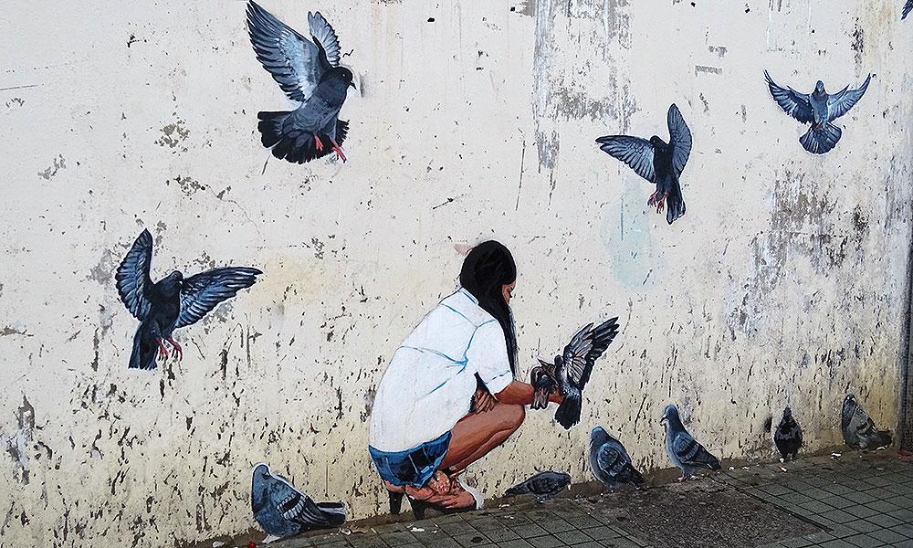 Streetart: Frau füttert Tauben