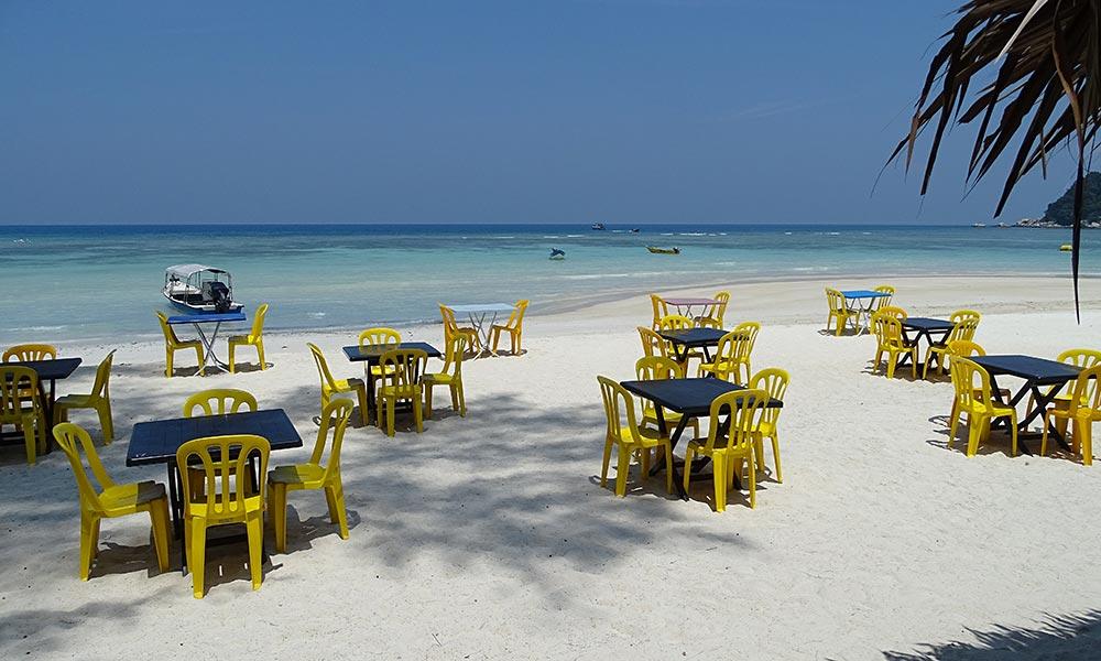 Gelbe Plastikstühle am Strand von Perhentian Besar