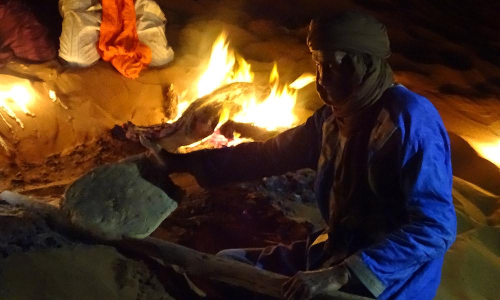 Mann nimmt Brot aus der Asche