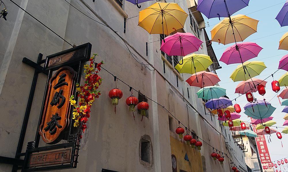 Straße mit Regenschirmen am Himmel