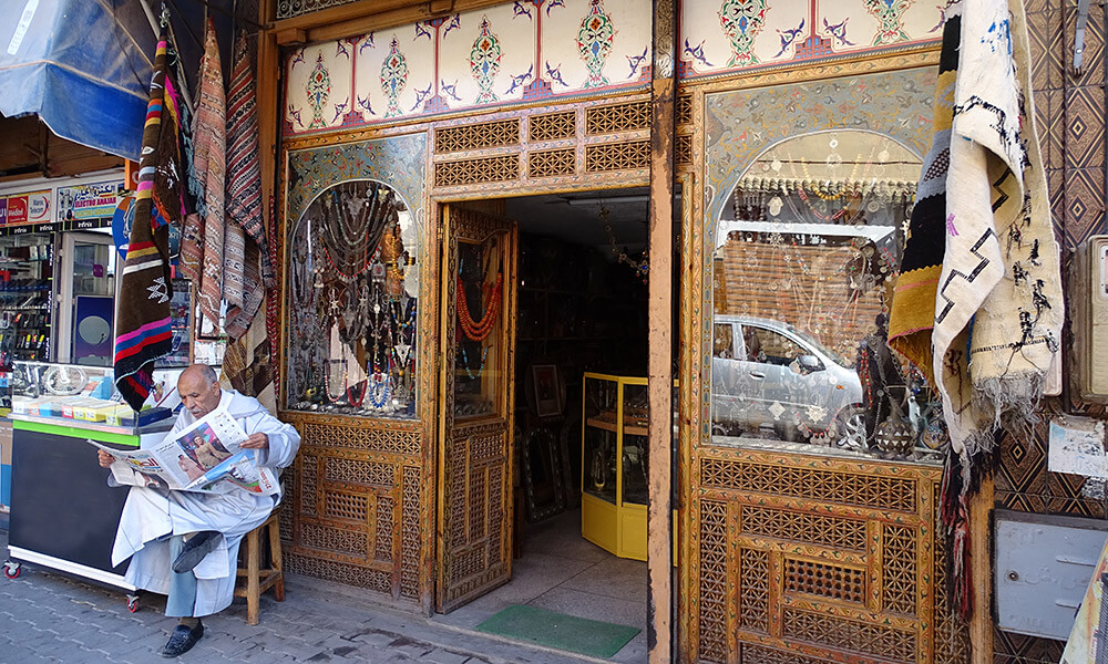 Mann mit Zeitung sitzt vor Geschäft in Taroudant