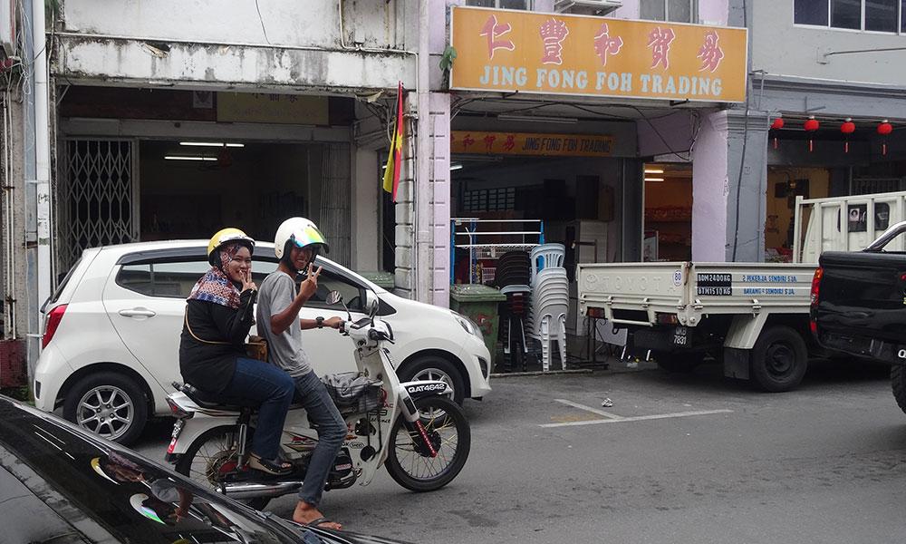 Mann und Frau auf Moped machen das Peace-Zeichen
