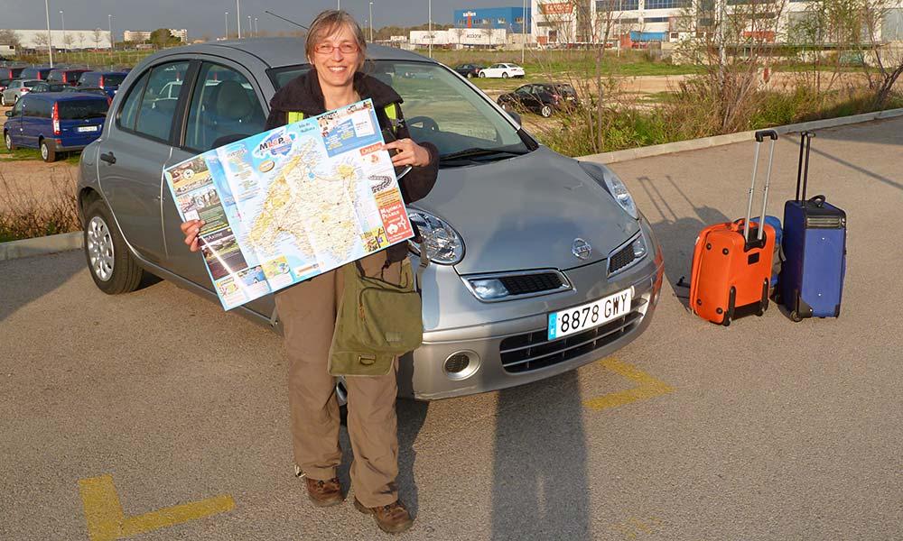 Frau mit Landkarte vor Auto