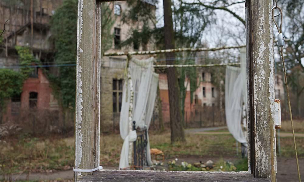 Blick durch Fensterrahman auf altes Haus