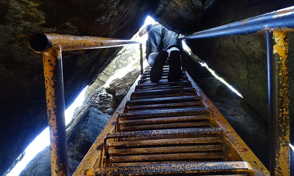 Auf Leiter durch enge Felsspalte