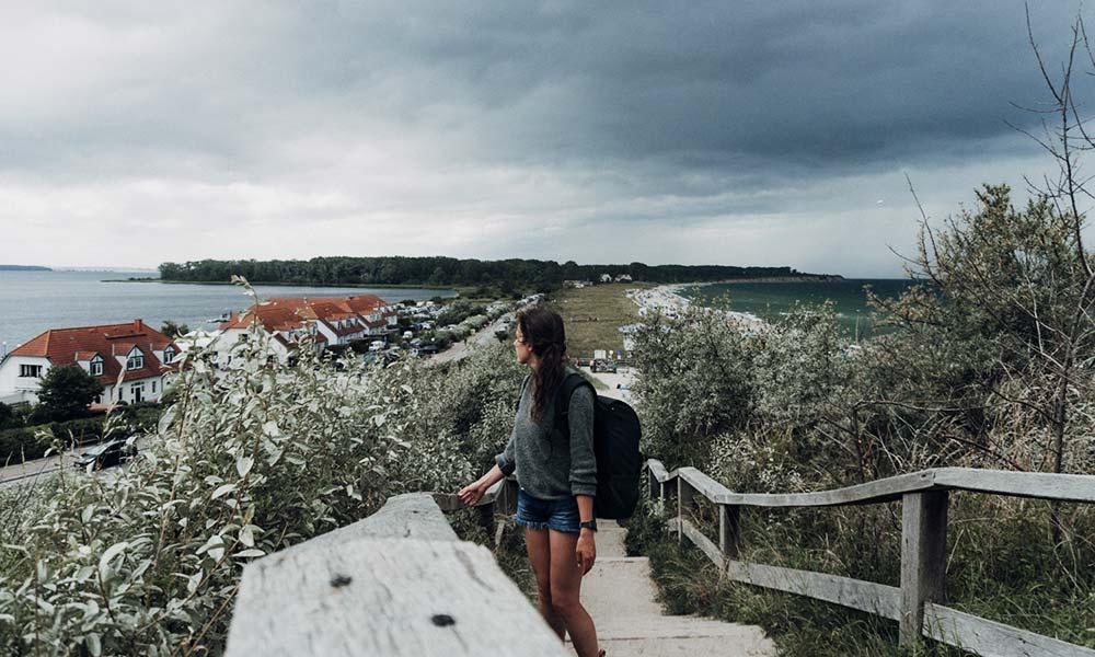 Frau auf Treppe mit Blick aufs Meer