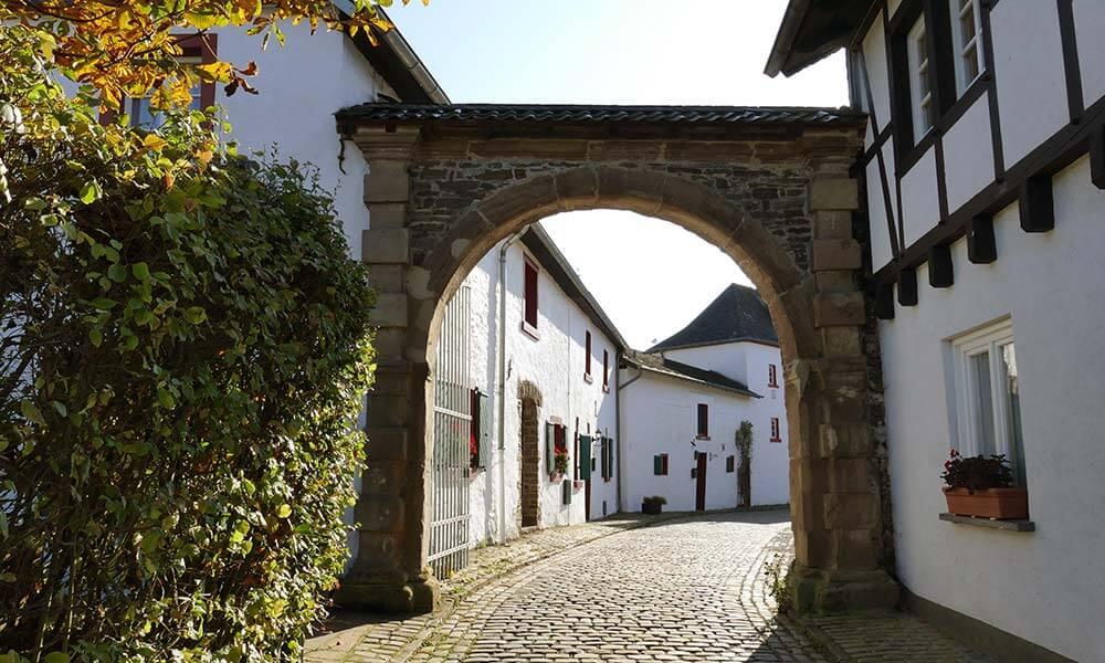 In Reifferscheid: Straße mit Kopfsteinpflaster und weißen Häusern hinter einem Tor