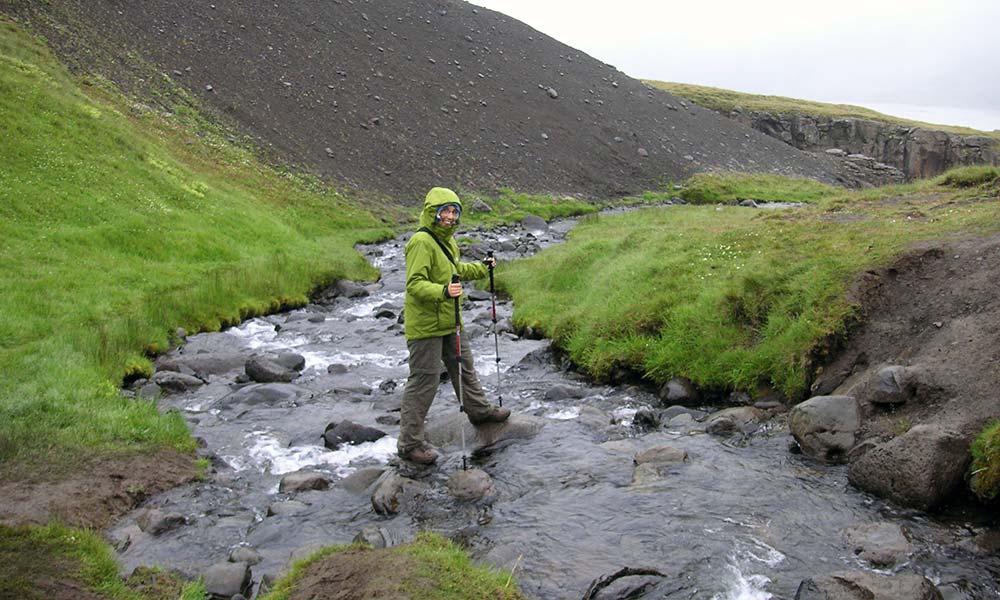 Wanderer mit Stücken bei Flussüberquerung