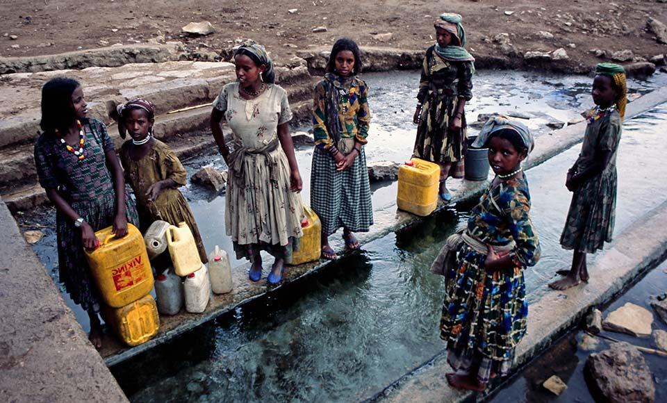 Afrikanische Kinder an einer Wasserstelle