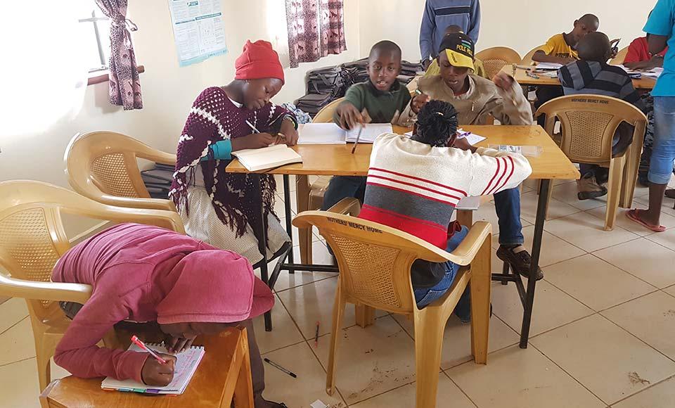 Afrikanischr Kinder schreiben am Tisch