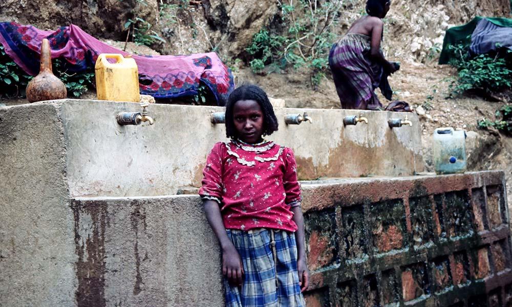 Mädchen vor Reihe mit Wasserhähnen