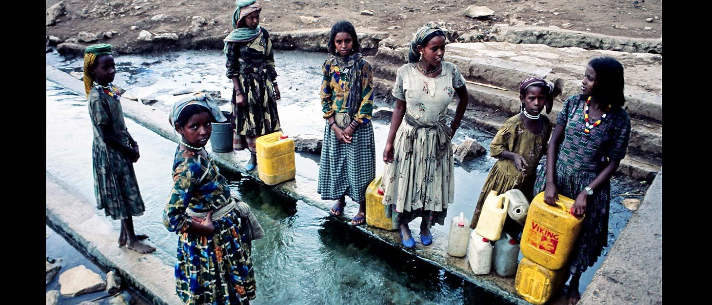 Frauen und Mädchen in Äthiopien holen Wasser an sauberer Wasserstelle