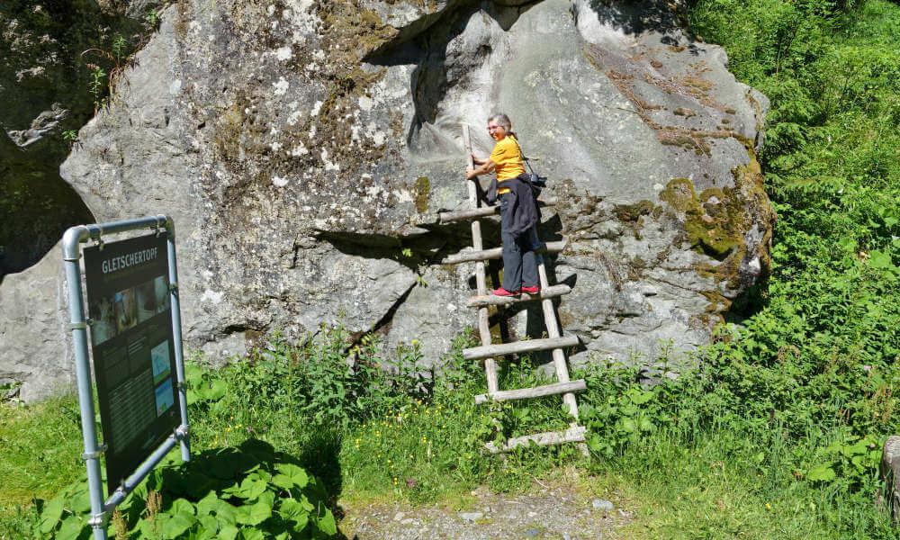 Frau auf Holzleiter an einer Felswand