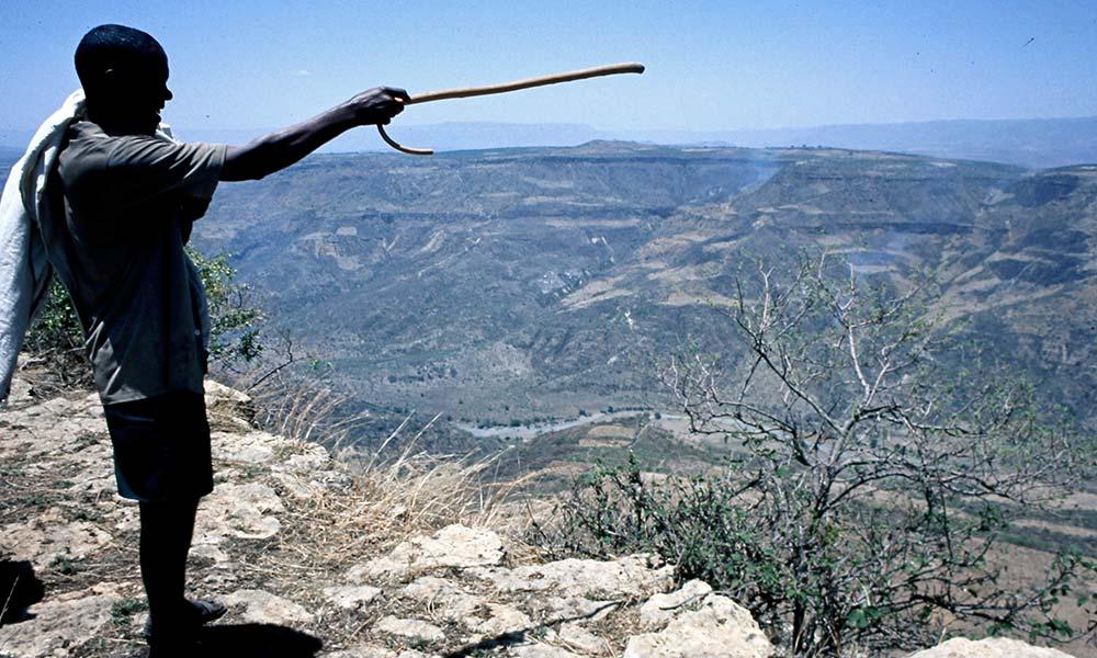 Mann in Äthiopien zeigt mit seinem Stock über die Berge